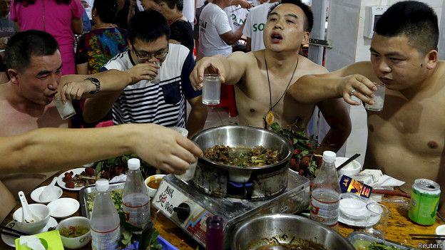 Hombres comiendo carne de perro