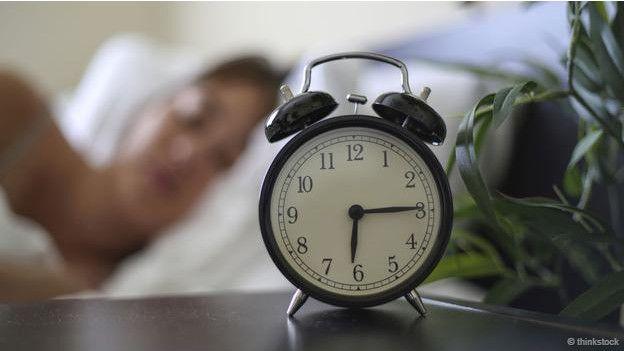 Una persona y un reloj despertador