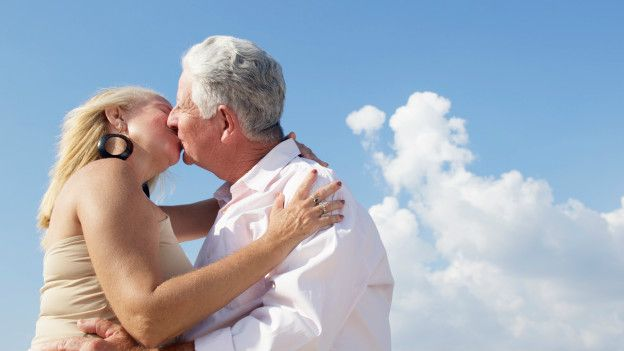 Dos adultos mayores dándose un beso