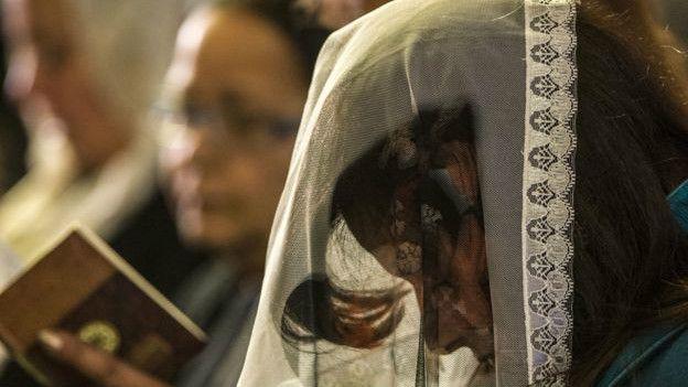 Una mujer reza en un templo