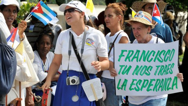 Unos fieles esperan a ver al papa en su recorrido por La Habana.