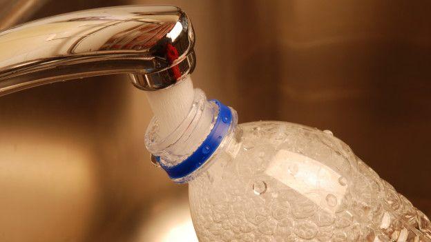 Botella de plástico llenándose con agua del grifo