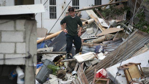 Un hombre se para en medio de los escombros
