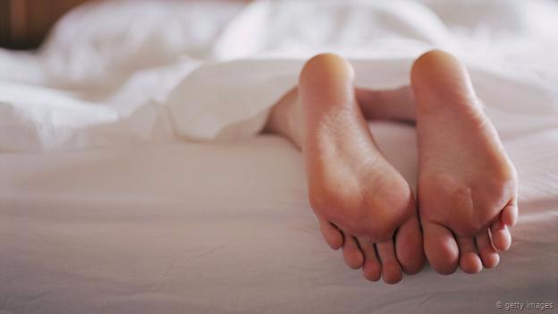 Unos pies sobresaliendo de una cama