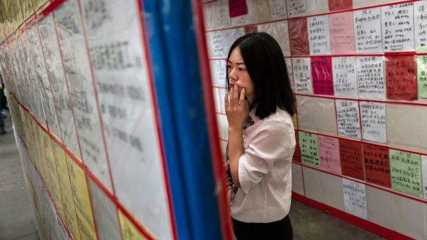 Jovem vê vagas de emprego em centro de Yiwu, na China (Foto: Kevin Frayer/Getty Images)