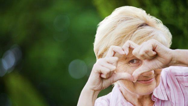 Una mujer mayor haciendo un símbolo de corazón con la mano