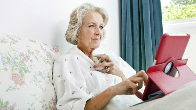 Una adulta mayor usando una tableta