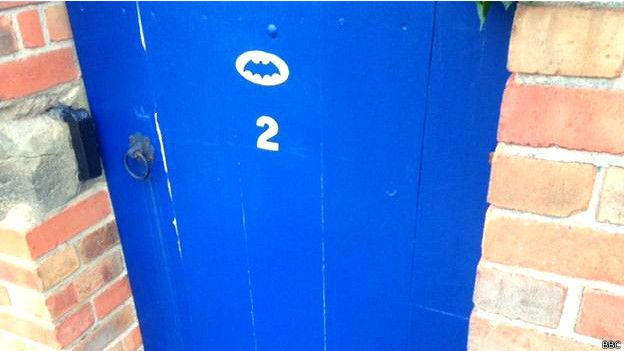 Puerta de una casa en Gotham con un símbolo de Batman