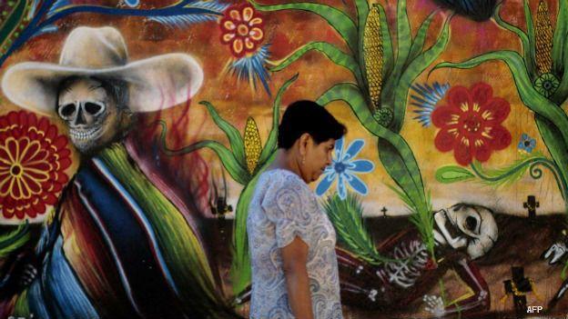 Una mujer pasa frente a un mural por Día de Muertos en Tixtla, Guerrero