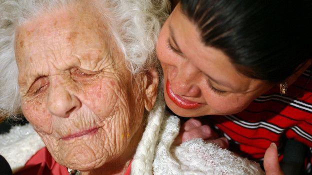 Mujer de más de cien años junto a familiar