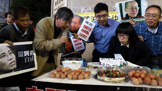 香港支联会秘书李卓人(左二)与示威者在铜锣湾集会上为刘晓  波的生日蛋糕吹蜡烛(28/12/2015)