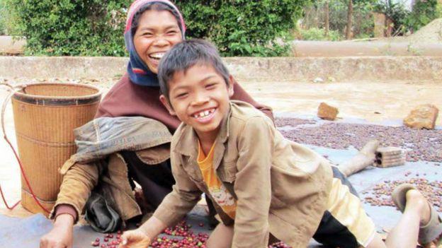 Chị H'Kinie cùng con trai lớp 4 bên cạnh những hạt cà phê lép mới đi mót về