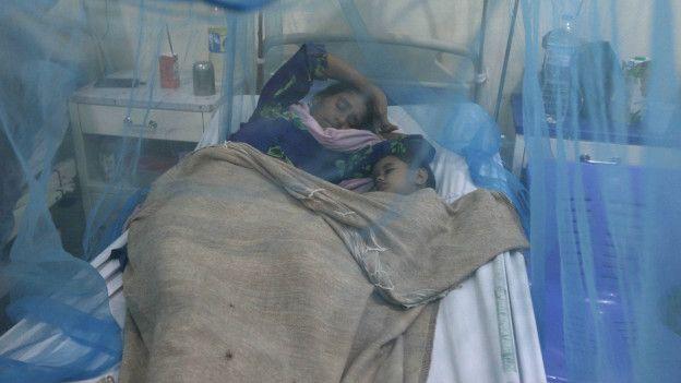 Una mujer y su hijo duermen bajo un mosquitero.