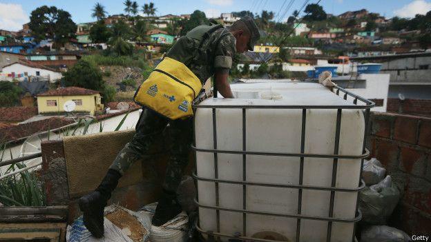 Soldado inspeccionando un tanque de agua en busca de larvas del mosquito trasmisor de zika