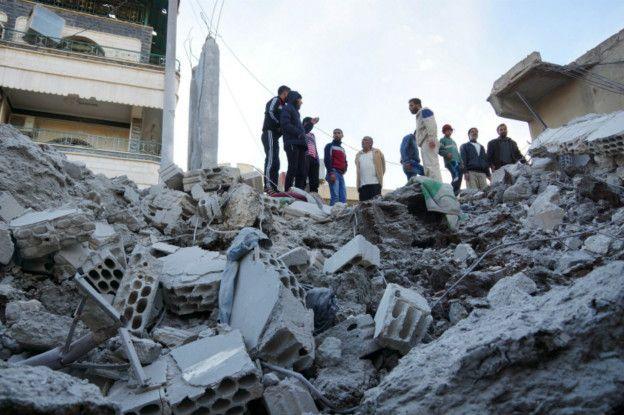 Мирные жители на развалинах дома