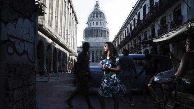 Una mujer posa con un vestido estampado con el Capitolio de La Habana de fondo
