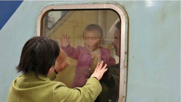 Una mujer saluda a su hijo, mientras se aleja en un tren.
