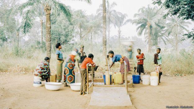 Mujeres y niños recogen agua de un pozo en Osukputu, Nigeria.