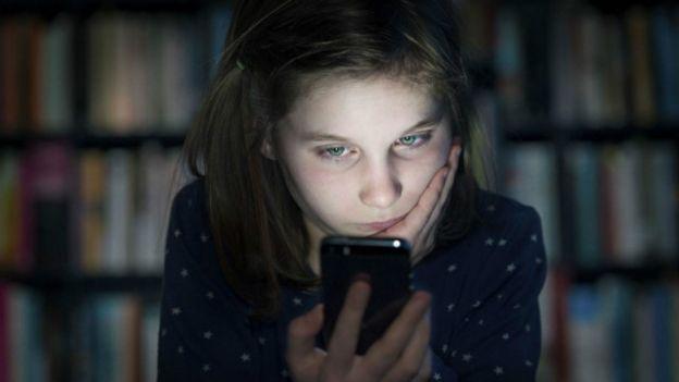 Una niña mirando preocupada un teléfono
