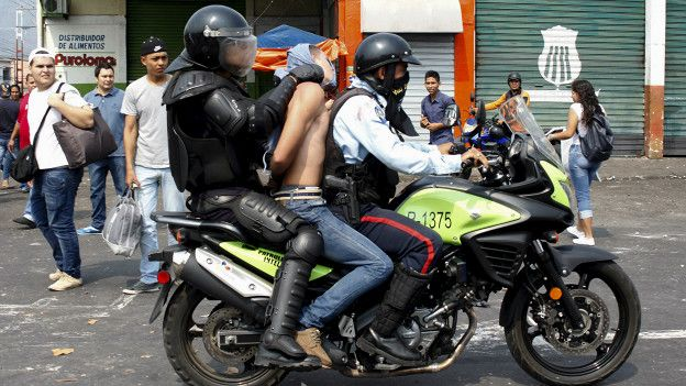 Dos policías con un detenido.