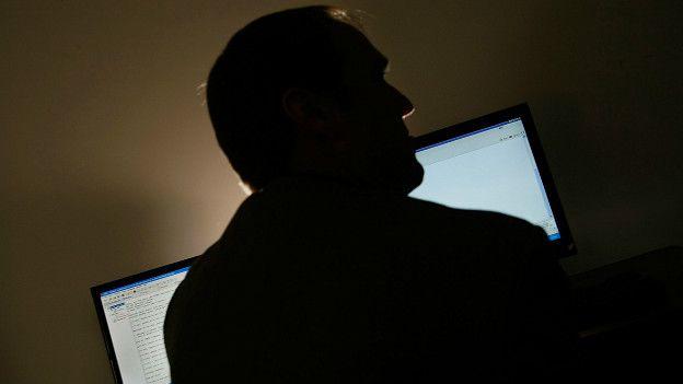 Hombre de espalda a dos pantallas
