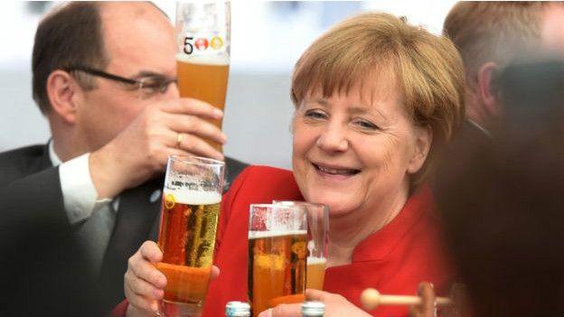 Ángela Merkel brindando con cerveza