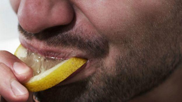Una persona chupado una rebanada de limón
