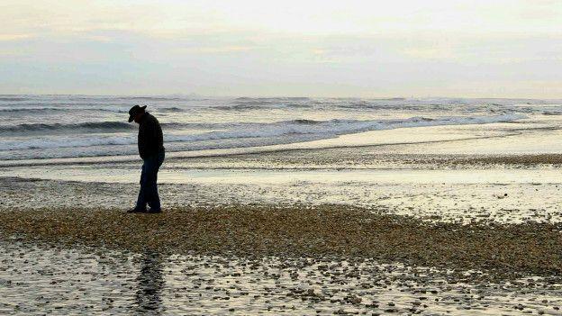 Un hombre camina por una playa llena de moluscos