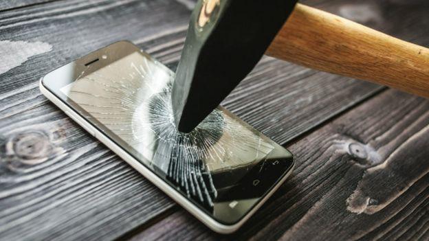 Una persona dándole un martillazo a un teléfono