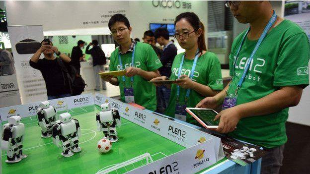 Alumnos jugando fútbol de mesa con tablets