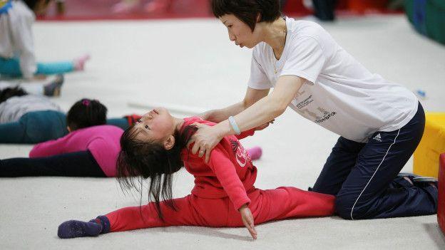 Representantes de la Escuela de Atletismo Amateur para Jóvenes de Shanghái Yangpu se pasean por los parvularios para promocionar la gimnasia entre padres y alumnos.