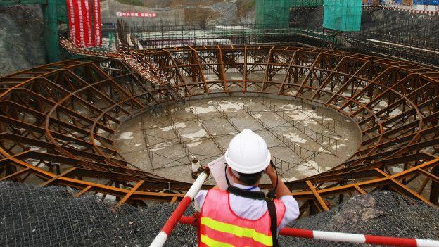 Un hombre frente a una construcción de una planta nuclear