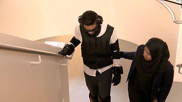 Estudante de 23 anos precisou de ajuda para subir escadas com o traje (BBC)