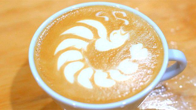 Taza de latte con dibujos en la espuma