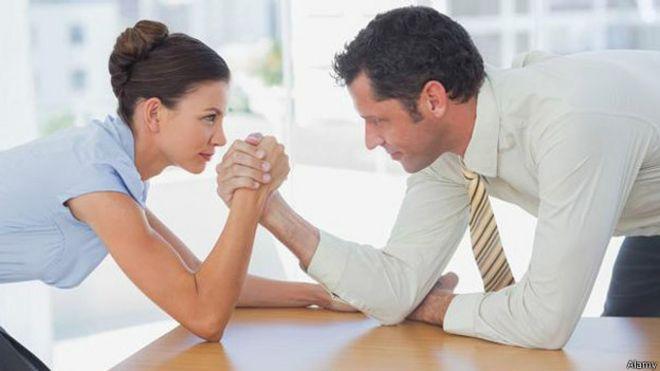 Dos personas haciendo una pulseada en el trabajo