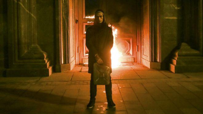 Павленский на фоне горящей двери здания ФСБ