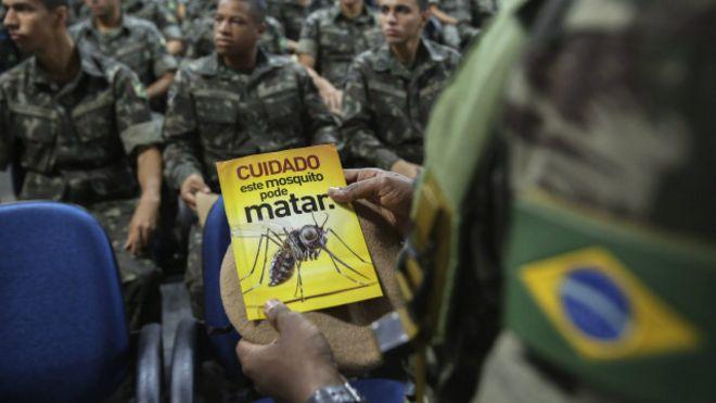 Un guardia sostiene un panfleto que alerta sobre el virus zika