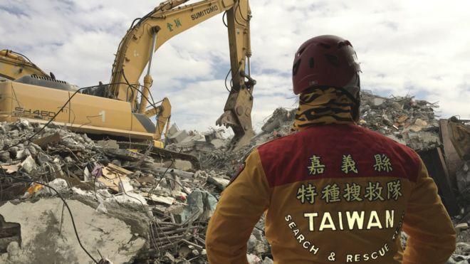 一名救援人员站在倒塌的维冠金龙大楼废墟上。维冠金龙大楼的倒塌导致重大伤亡,开发商已接受司法调查。