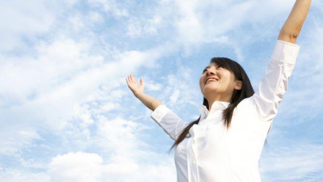 Mujer levantando los brazos al cielo
