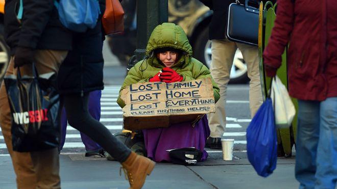 Una mujer se prueba un collar de diamantes y una indigente pide limosna en Nueva York