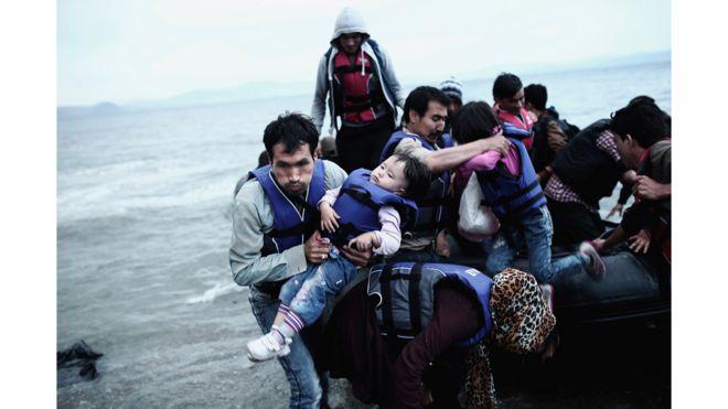 Un refugiado afgano carga a su hijo al llegar a la isla griega de Kos, luego de cruzar parte del mar Egeo entre Turquía y Grecia, en mayo de 2015