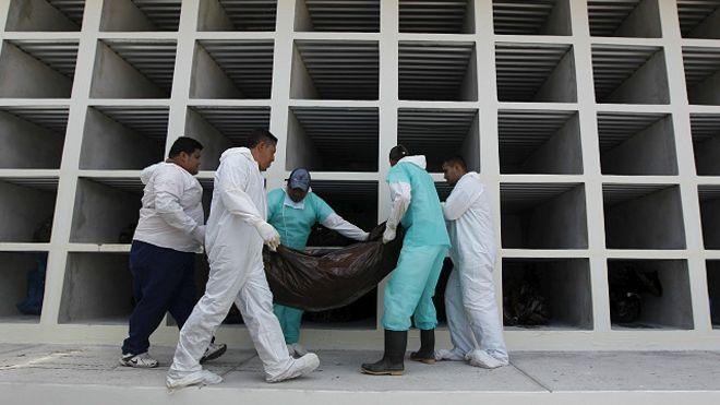 Trabajadores de una morgue cargan un cadáver