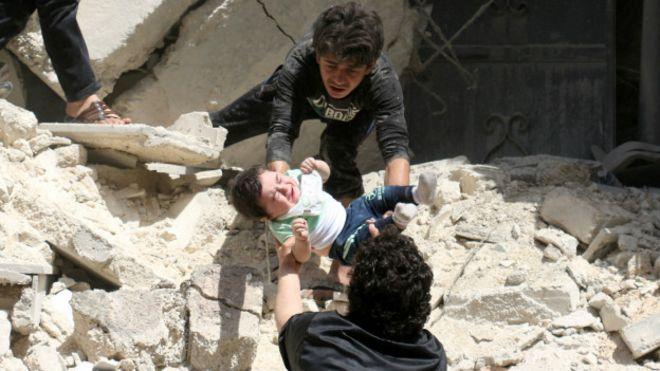 Dos jóvenes rescatan a un bebé de un edificio afectado por los ataques en Alepo.