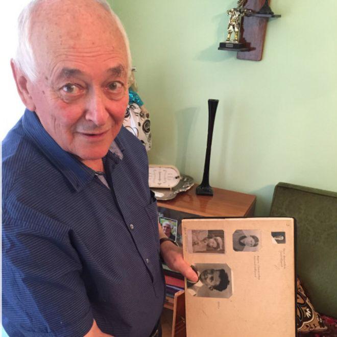 79-летний Василий Михайловский держит в руках альбом со своими детскими фото. Он выжил в Бабьем Яру