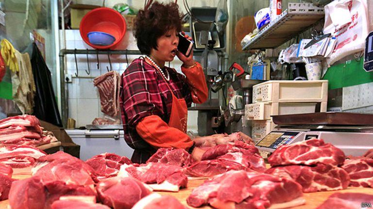 Mujer en un mercado en China vendiendo carne