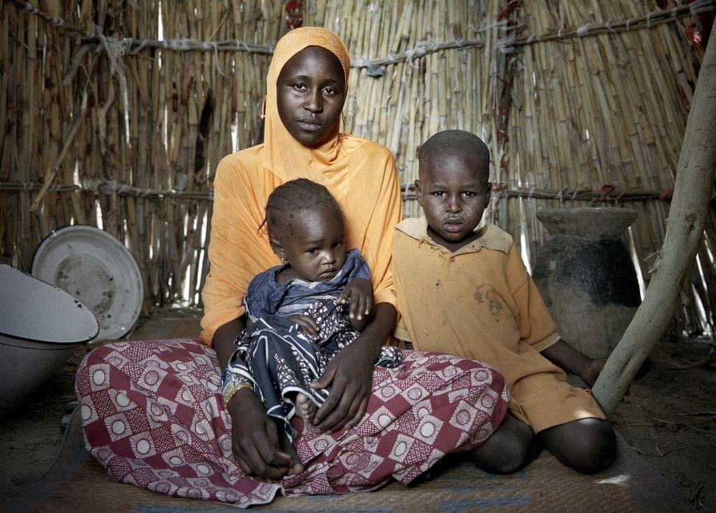 20 yaşındaki chelou Bossomi, 18 aylık kızı Khalfoumi ve oğlu Abba, 4'üncü sırada, Mémé'nin eteklerinde yerinden edilmiş kişiler.