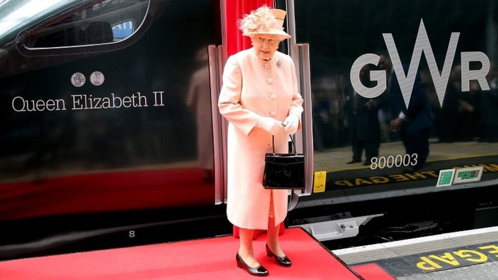 The Queen looks at her name on a train