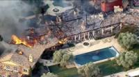 Aerial shot shows a large mansion totally destroyed by fire