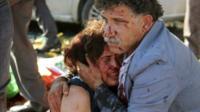 An injured man hugs an injured woman