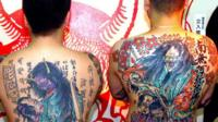 Two men with tattoos covering their backs